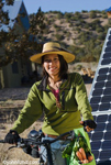 A Native American woman riding a bicycle with solar panels visible behind her. The woman has a straw hat to protect her from the sun and she is wearing a green sweat shirt and riding gloves.